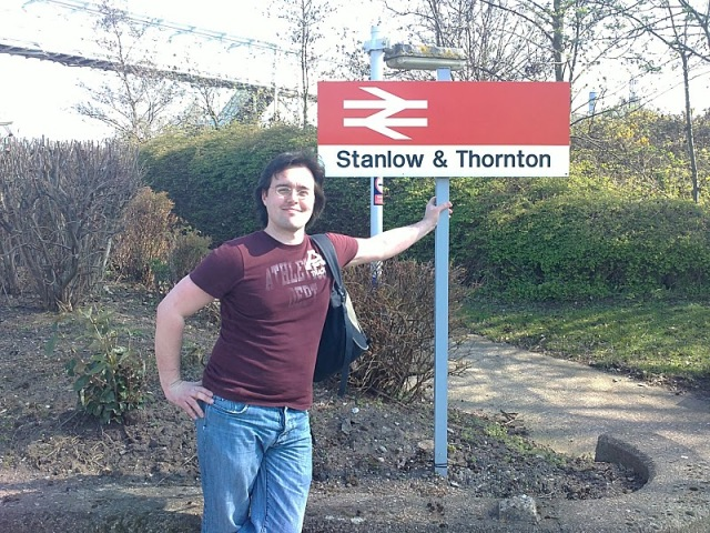 Scott in front of the Stanlow & Thornton station sign