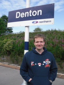 Photo of Robert standing under the Denton station sign