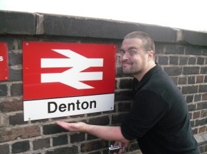 Scott stands in front of the sign at Denton station entrance