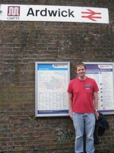 Photo of Robert Hampton standing under the Ardwick station sign