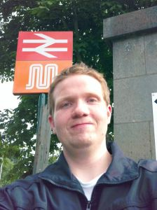 Photo of Robert posing underneath the Clifton station sign