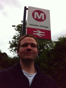Photo of Robert in front of the Hebden Bridge sign