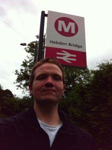 Photo of Robert in front of the Hebden Bridge sign