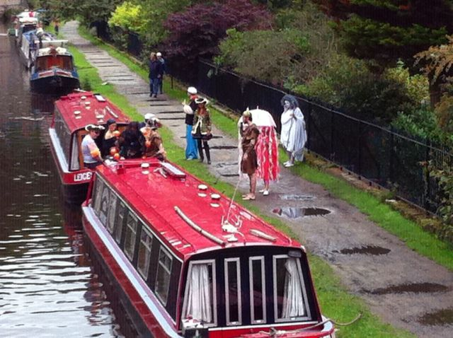 Photo of people boarding a canal barge dressed in costumes