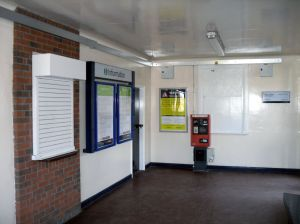 Photo of Interior of Acton Bridge Station Building, showing disused ticket window, posters and a Permit to Travel machine