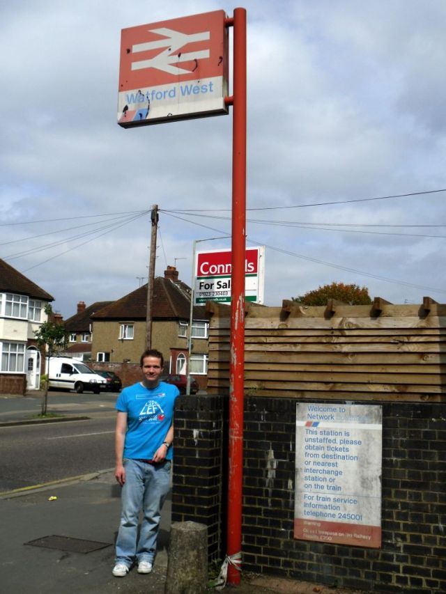 Photo of obert standing beneath Watford West roadside station sign