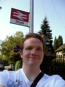 Photo of Robert Hampton underneath the Styal station sign
