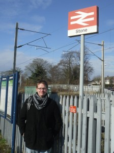 Photo of Robert posing under the Stone station sign