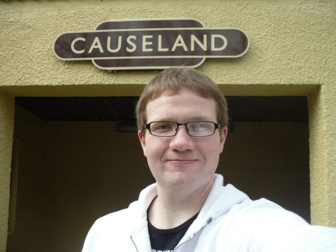 Photo of Robert standing underneath the Causeland station sign