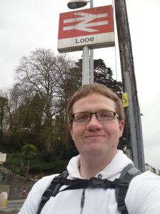 Photo of Robert standing under the Looe station sign