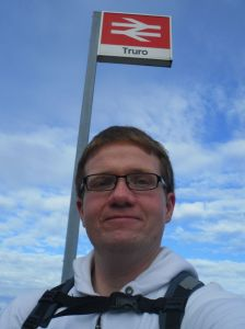 Robert standing under the Truro station sign