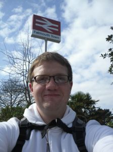 Photo of Robert standing under the Falmouth Town station sign