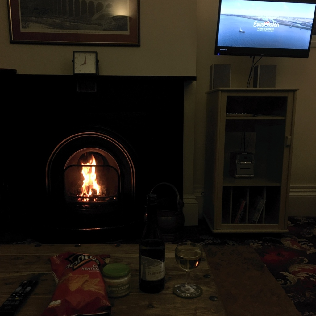 Cottage living room in the evening. A roaring fire in the fireplace. TV is showing the Eurovision song contest. On the table is a bottle of wine with a glass next to it, and a bag of Doritos with dip.