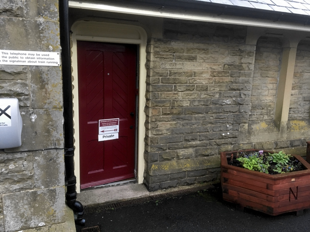Red door entrance to Booking Office Cottage from the platform at Kirkby Stephen station