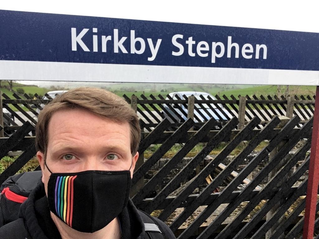 Robert standing in front of platform sign at Kirkby Stephen