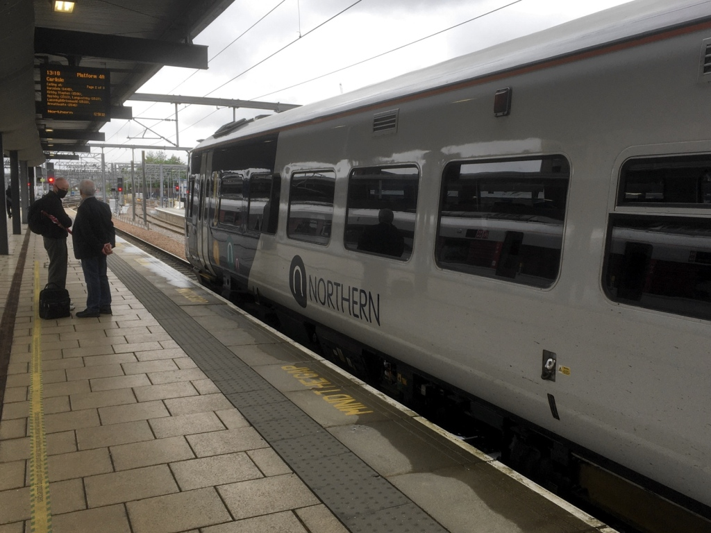 Northern class 158 train in a platform at Leeds. A couple of intending passengers stand on the platform waiting. Information display indicates this is the 1318 to Carlisle