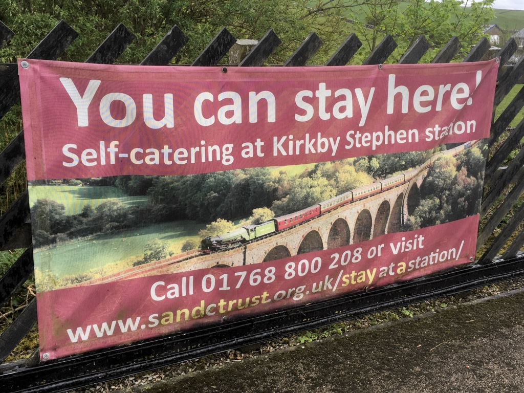 """Banner attached to fence at Kirkby Stephen station. """"You can stay here! Self-catering at Kirkby Stephen station"""" with a photo of a steam train crossing a viaduct."""