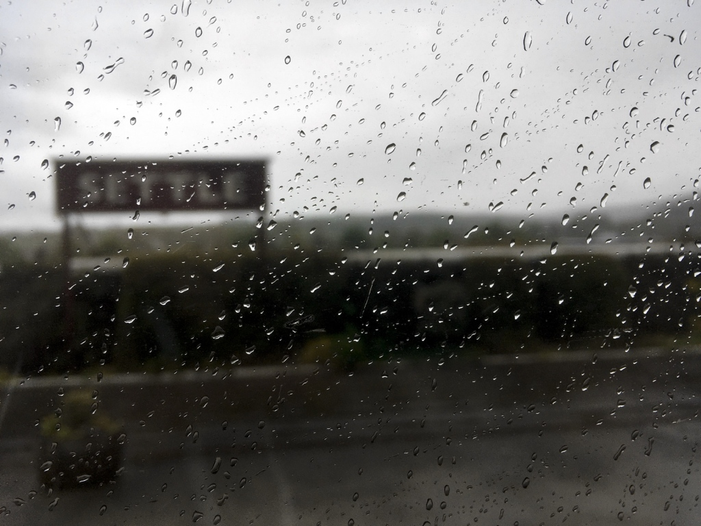 Station nameboard at Settle, seen through a train window partially obscured by raindrops.